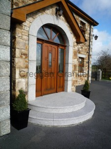 Silver-grey, arched granite door surround along with silver-grey granite steps .