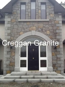 Silver-grey, arched granite door surround